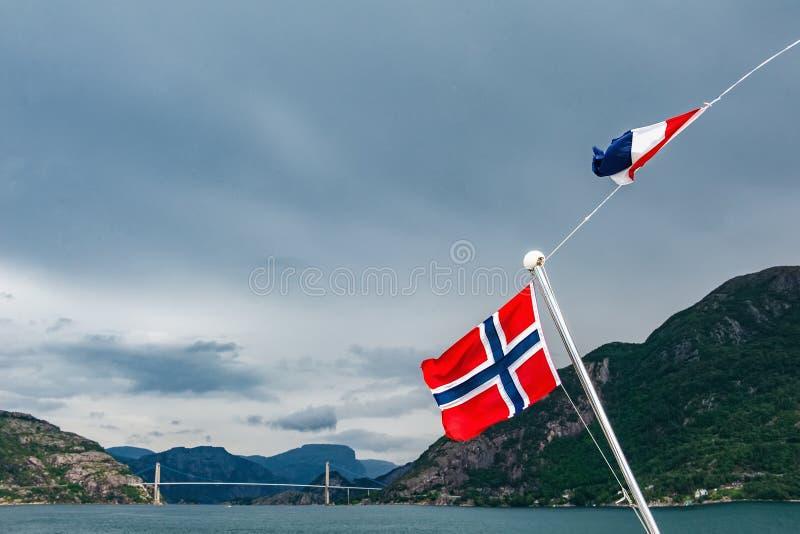 在山包围的海湾的挪威旗子 多云和多雨天气,剧烈的天空 库存照片
