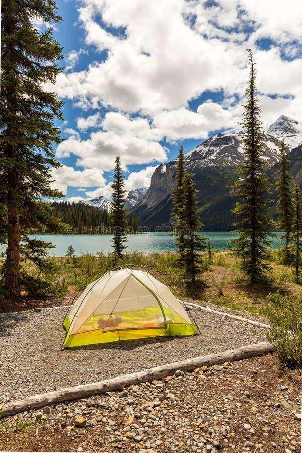 在山包围的高山湖海岸线的帐篷 免版税库存照片