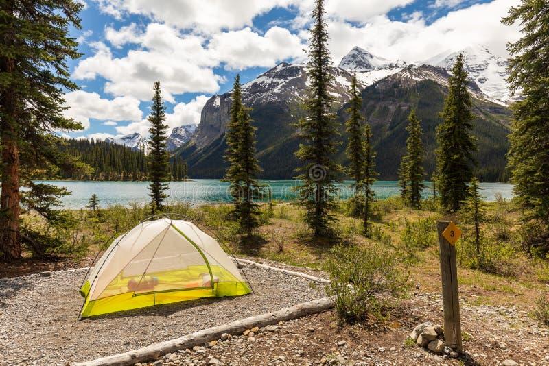 在山包围的高山湖海岸线的帐篷 免版税库存图片
