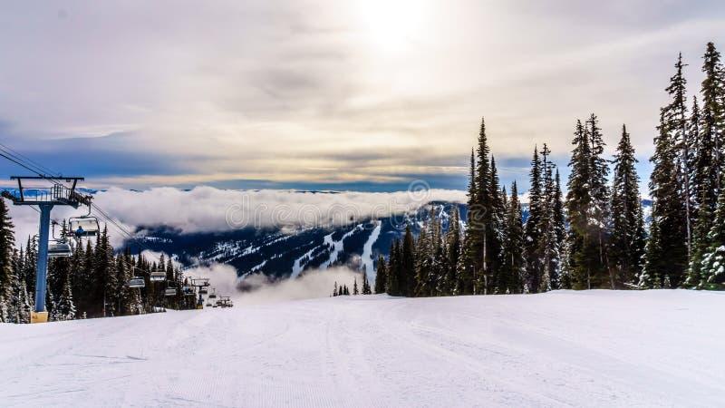 在山和围拢太阳峰顶的滑雪倾斜的日落 库存图片