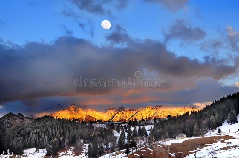 在山和月亮的日落 免版税库存图片