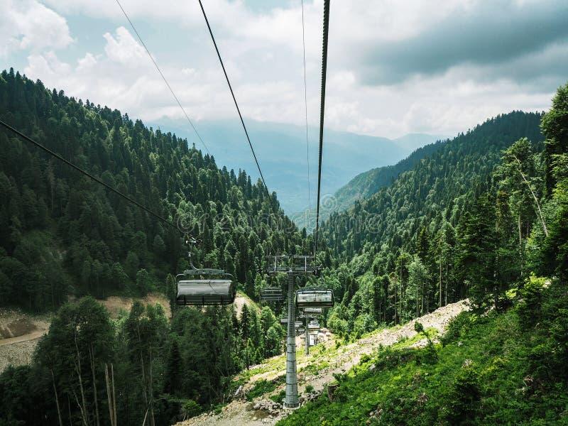 在山和森林背景的驾空滑车 免版税库存图片