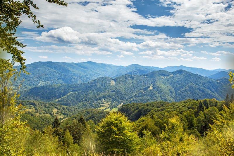 在山和深蓝天空的夏天风景与云彩 免版税库存照片