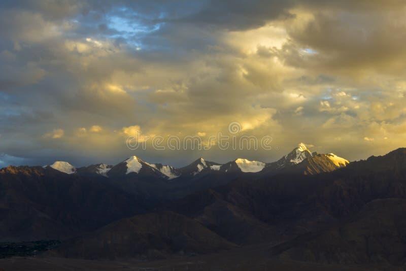 在山和美丽的日落天空的一个晚上在多雪的山峰 库存照片
