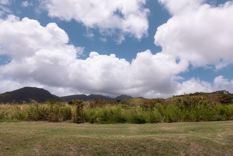 在山和草甸的美丽的天空 免版税库存照片