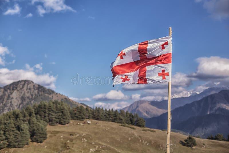 在山和蓝天的英王乔治一世至三世时期旗子在高加索 免版税库存图片