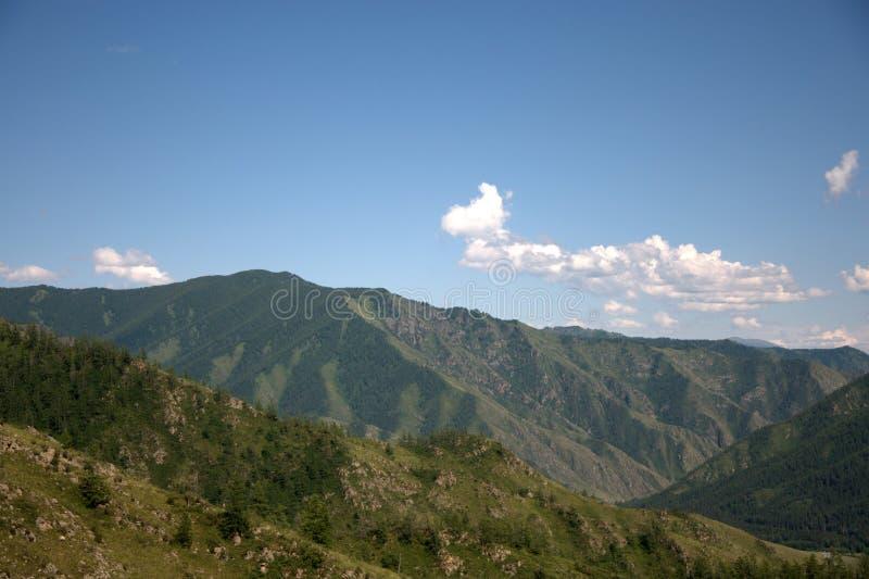 在山围拢的肥沃绿色山谷上的白色蓬松云彩 库存图片