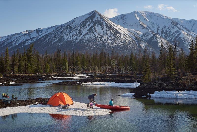 在山地形结合男人和妇女阵营的 与独木舟的湖岸 免版税库存图片
