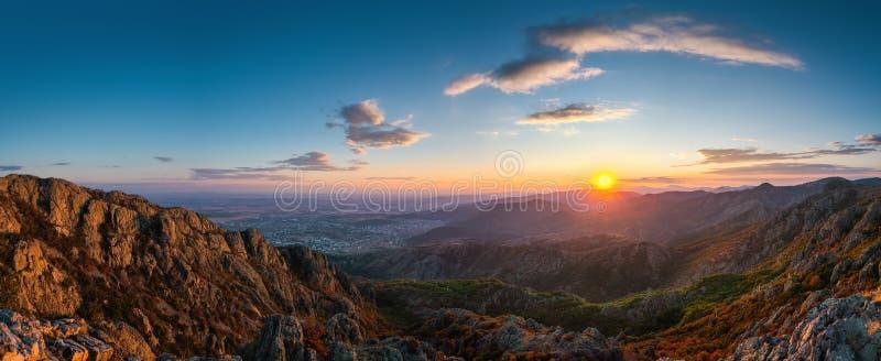 在山小山和城市,空中panora的美好的日落 免版税库存图片