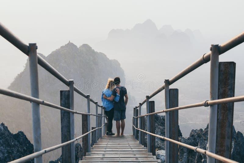 在山峰的年轻夫妇身分与去下来早晨日出有雾的台阶在Hpa-An,缅甸 库存图片