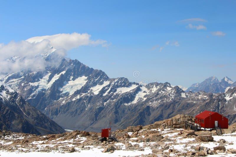 在山峰的红色小屋与雪在新西兰 库存照片