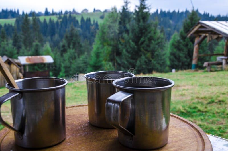 在山林背景下,三只带晨咖啡的金属杯 免版税库存照片