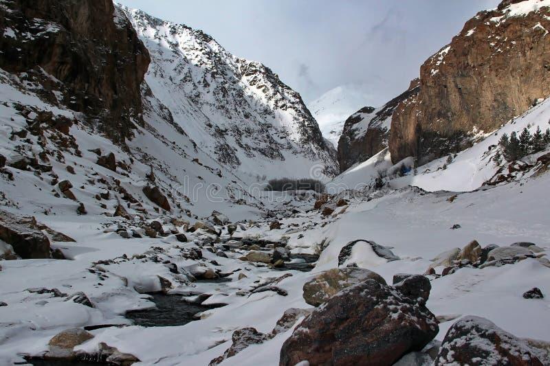 在山沟的山小河在高加索之间Elbrus的积雪覆盖的山 库存图片