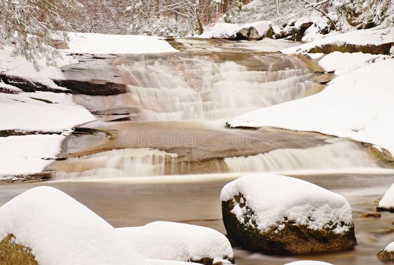 在山河的冬天 在用新鲜的粉末雪和懒惰水盖的小河的大石头与低级 图库摄影