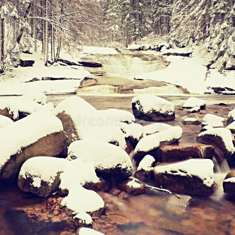 在山河的冬天 在用新鲜的粉末雪和懒惰水盖的小河的大石头与低级 库存照片