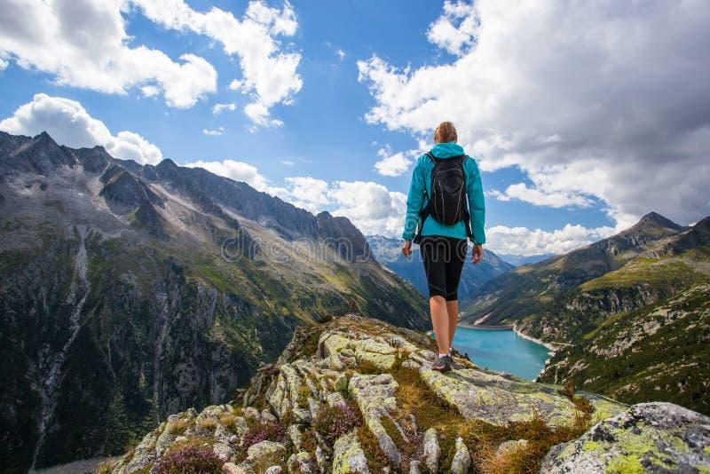 在山的上面的妇女远足者 库存图片