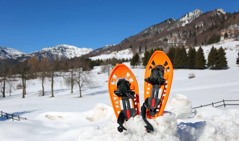 在山的两双橙色雪靴在与雪的冬天 免版税库存照片