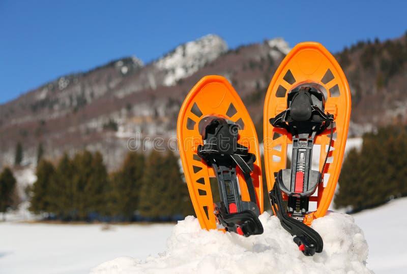 在山的两双橙色雪靴 免版税库存图片
