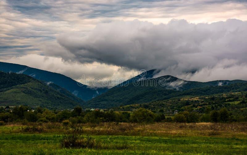 在山的云彩上升在阴暗早晨 免版税库存图片
