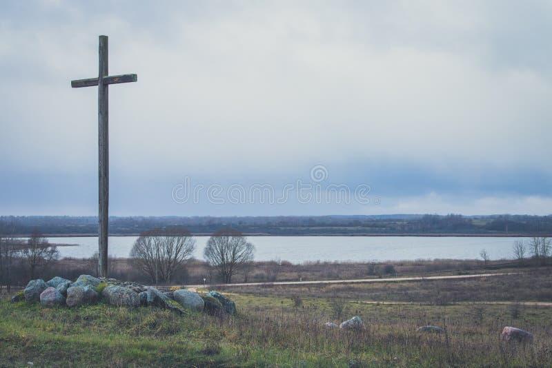 在山的农民木十字架在河岸,湖附近 库存照片