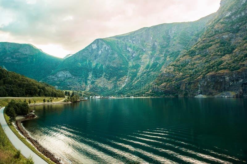 在山的剧烈的日落在挪威的海湾上 与反射的美丽的景色在水中 免版税库存图片