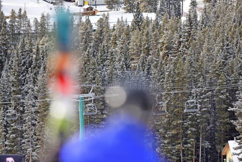 在山的升降椅与被弄脏的滑雪者 库存照片