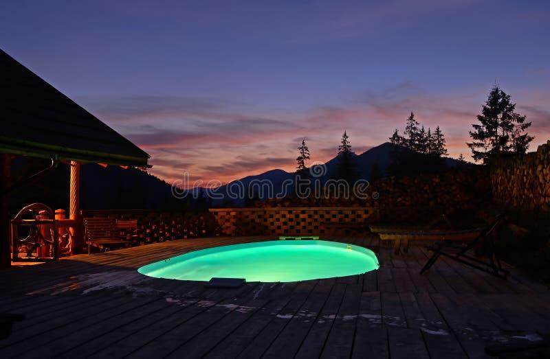 在山的卵形露天游泳场上流反对美丽的夏天日落和山的背景 的treadled 免版税库存图片