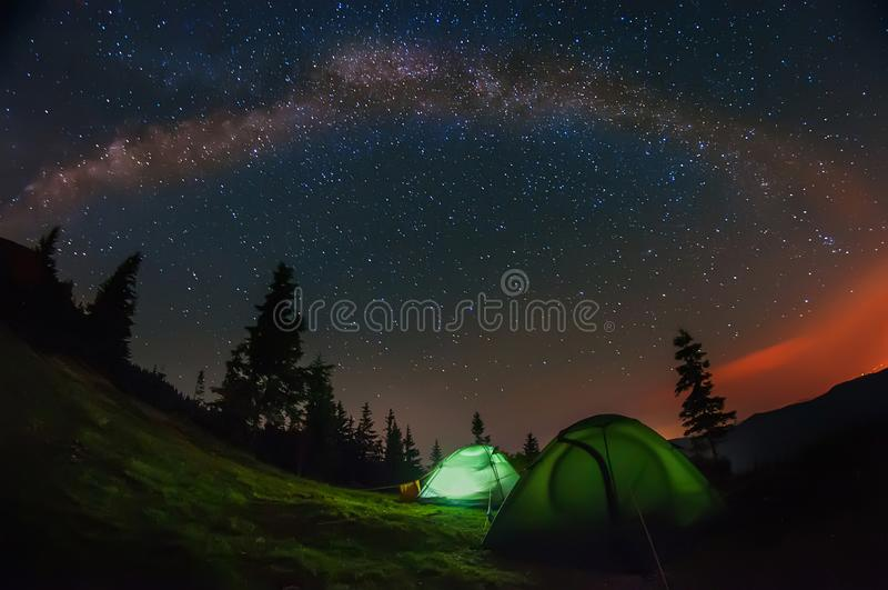 在山的夜照片 在清洁在满天星斗的天空下,对整个天空的银河的帐篷在帐篷上 库存图片