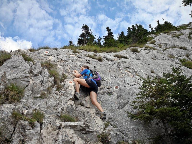 在山的妇女上升的岩石 库存照片