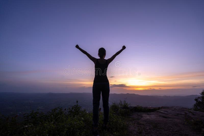 在山的妇女成功的远足的上升的剪影 免版税图库摄影