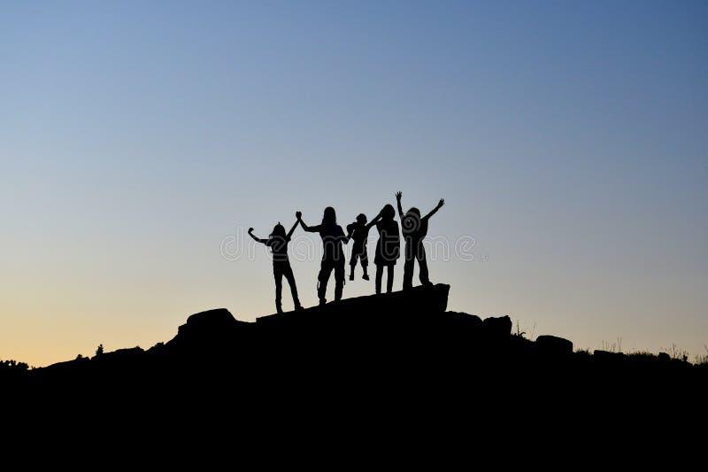 在山的山顶成功的家庭小组 库存照片