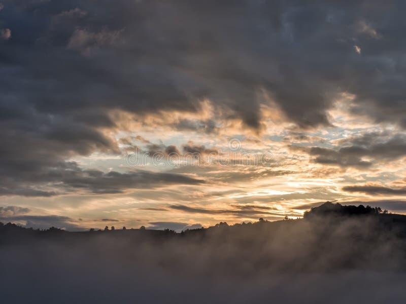 在山的峰顶的美好的日出光与树剪影的 免版税库存图片