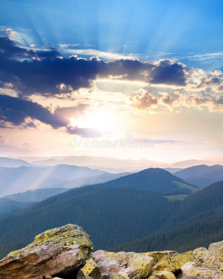 在山的庄严日出与光束-垂直 免版税库存照片