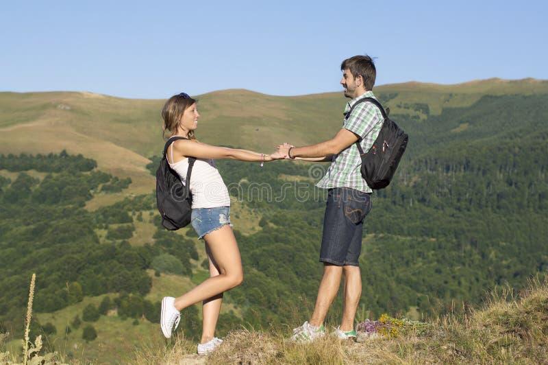 在山的愉快的远足者夫妇 免版税库存图片