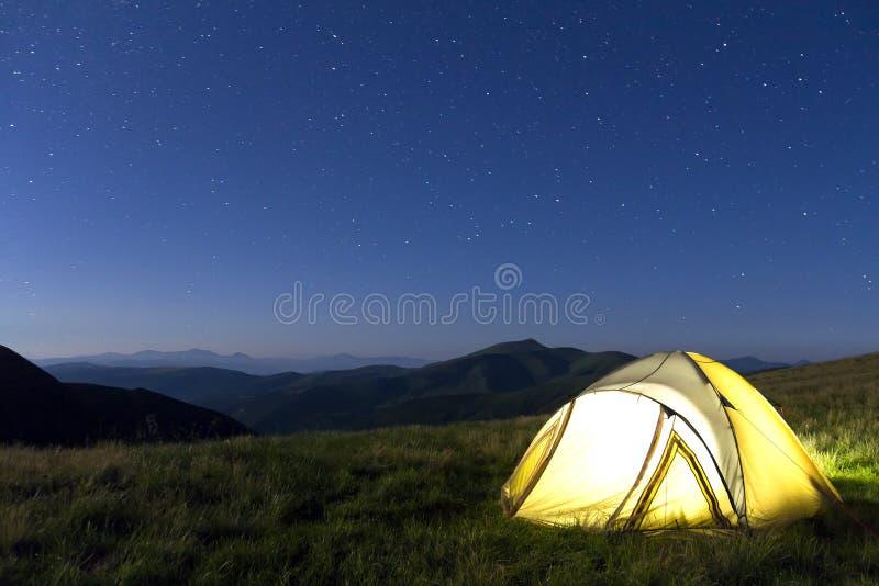 在山的旅游远足者帐篷在与星的晚上在天空 免版税库存照片