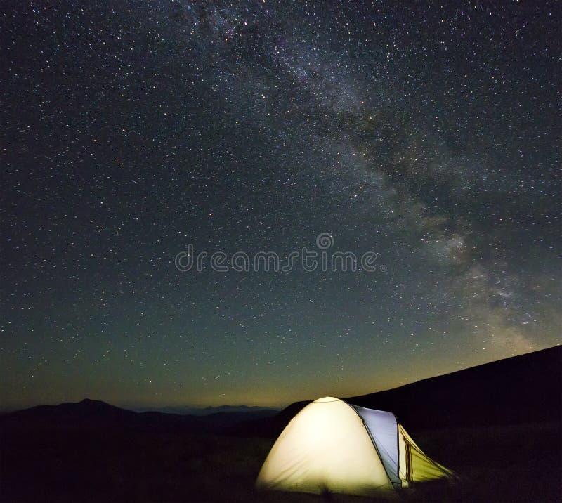 在山的旅游远足者帐篷在与银河的晚上担任主角i 免版税库存照片