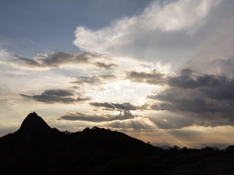 在山的日落光束在多云天空 免版税图库摄影