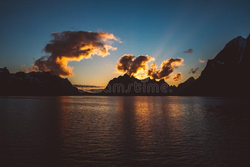 在山的日落由海 山的剪影 beautiful clouds 免版税库存图片