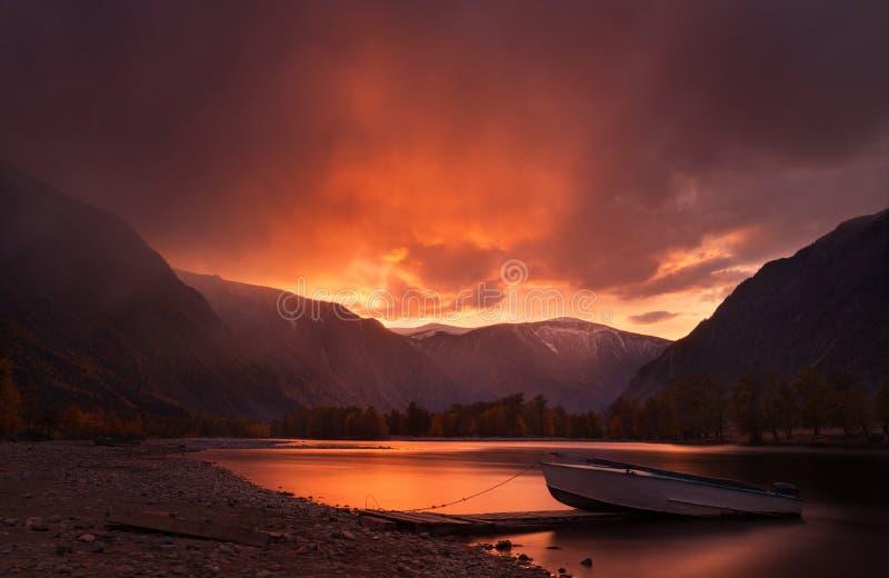 在山的日落 在红色口气的迷人秋天山风景与日落天空、河有反射的和偏僻的小船 免版税库存照片