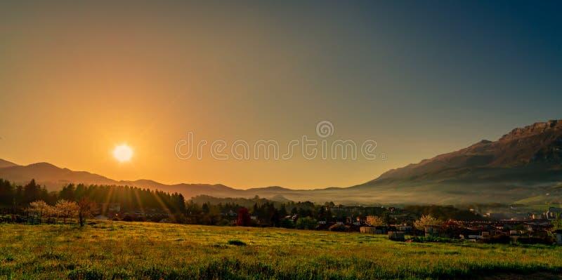 在山的早晨日出与清楚的天空蔚蓝 草地和杉木森林在岩石山附近的乡村 ? 库存照片