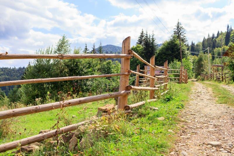在山的木村庄篱芭在土路附近 免版税库存图片