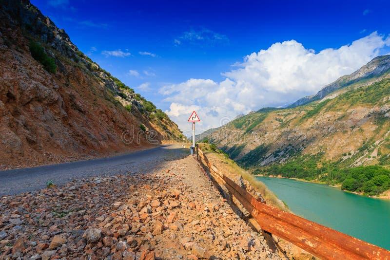 在山的残破的路和危险弯签字 易碎汽车概念 库存图片
