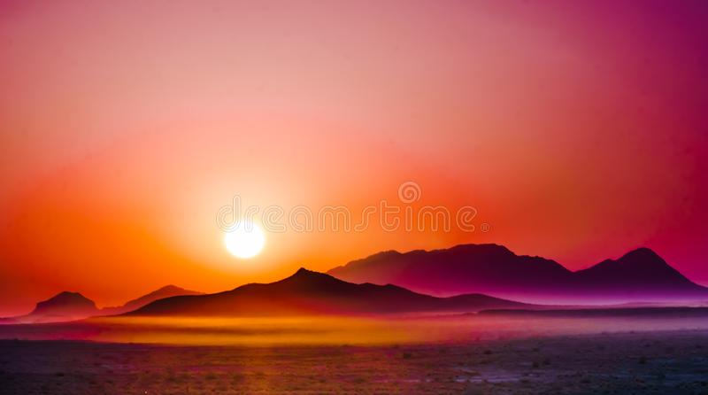 在山的紫色日出在沙漠 库存图片