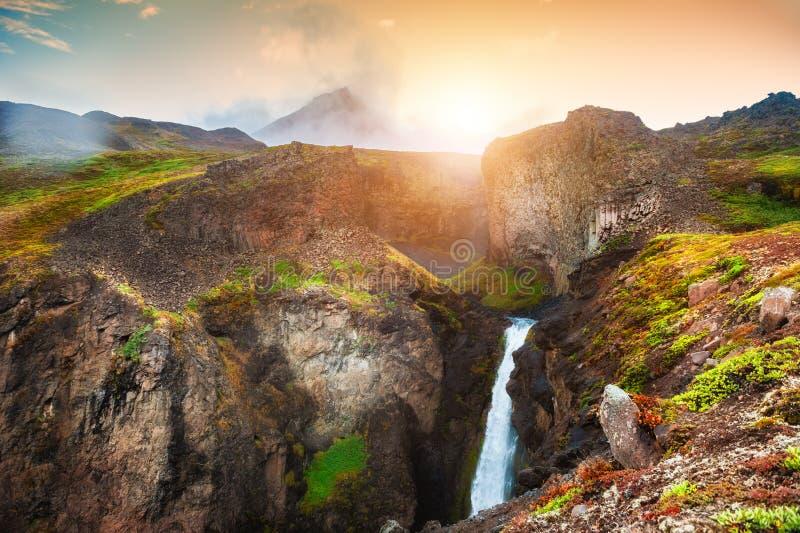 在山的美丽的瀑布在日落 E 免版税库存照片