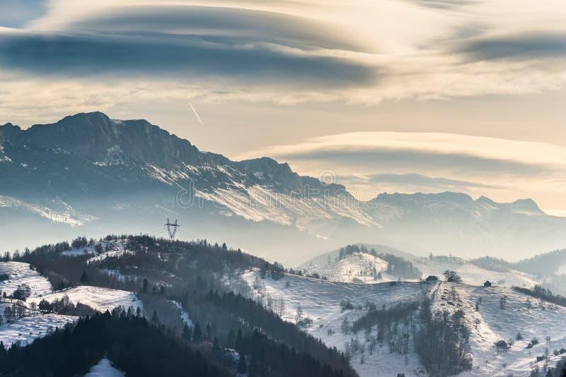 在山的美好的冬天风景与双突透镜的云彩和雪 库存照片