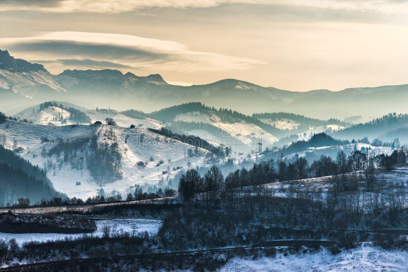 在山的美好的冬天风景与双突透镜的云彩和雪 库存图片