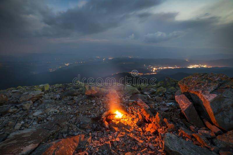 在山的美好的夏夜 明亮的火在岩石m烧 免版税库存图片
