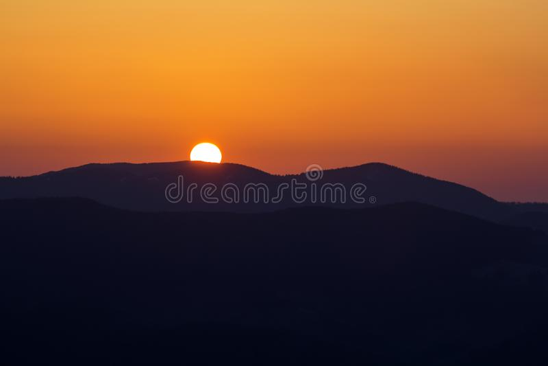 在山的美好的日落 大明亮的白色太阳宽全景视图在剧烈的橙色天空的在黑暗的山脉 免版税库存图片
