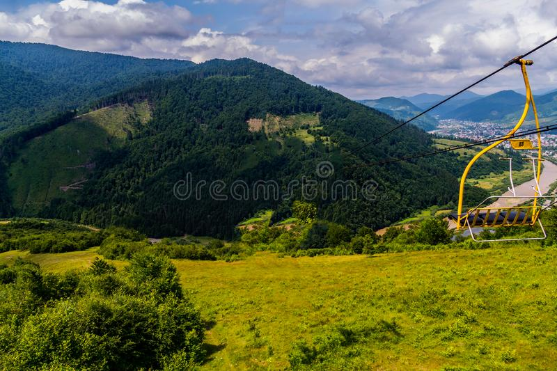 在山的美好的风景从滑雪电缆车在夏天,在山的脚的一个小镇附近 免版税库存图片