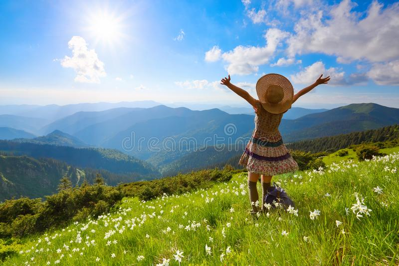 在山的草坪使礼服的,长袜行家女孩环境美化,并且草帽停留观看与云彩的天空 免版税库存图片